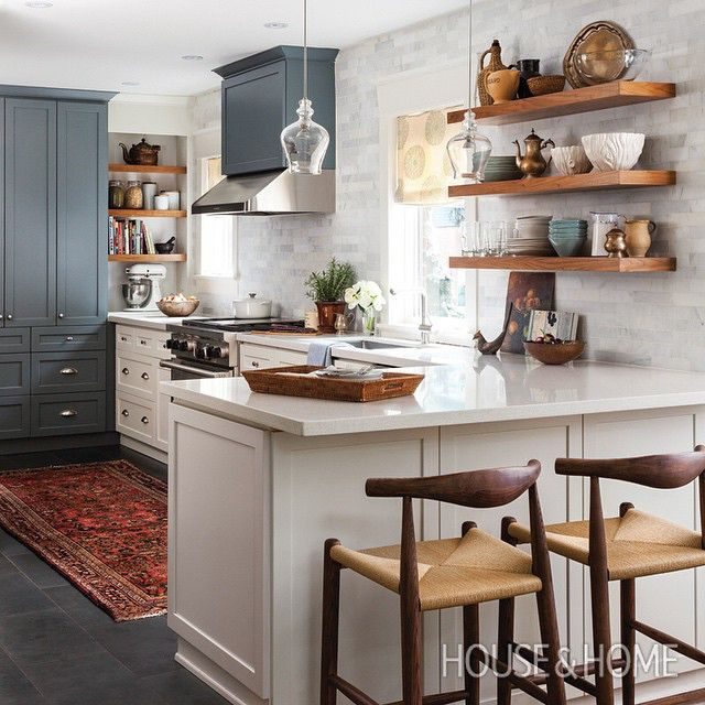 We love this warm kitchen with two-tone cabinets and wood shelving by Qanūk @qanukinteriorsinc [Photo: Donna Griffith]