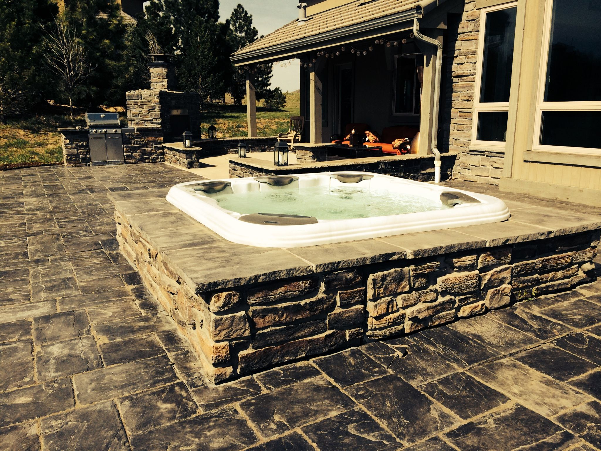 this bullfrog hot tub in castle rock colorado has beautiful stone surround that matches the