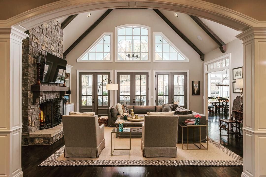 living room: vaulted ceilings, rock fireplace, tall windows, open to kitchen #vaultedceilingdecor