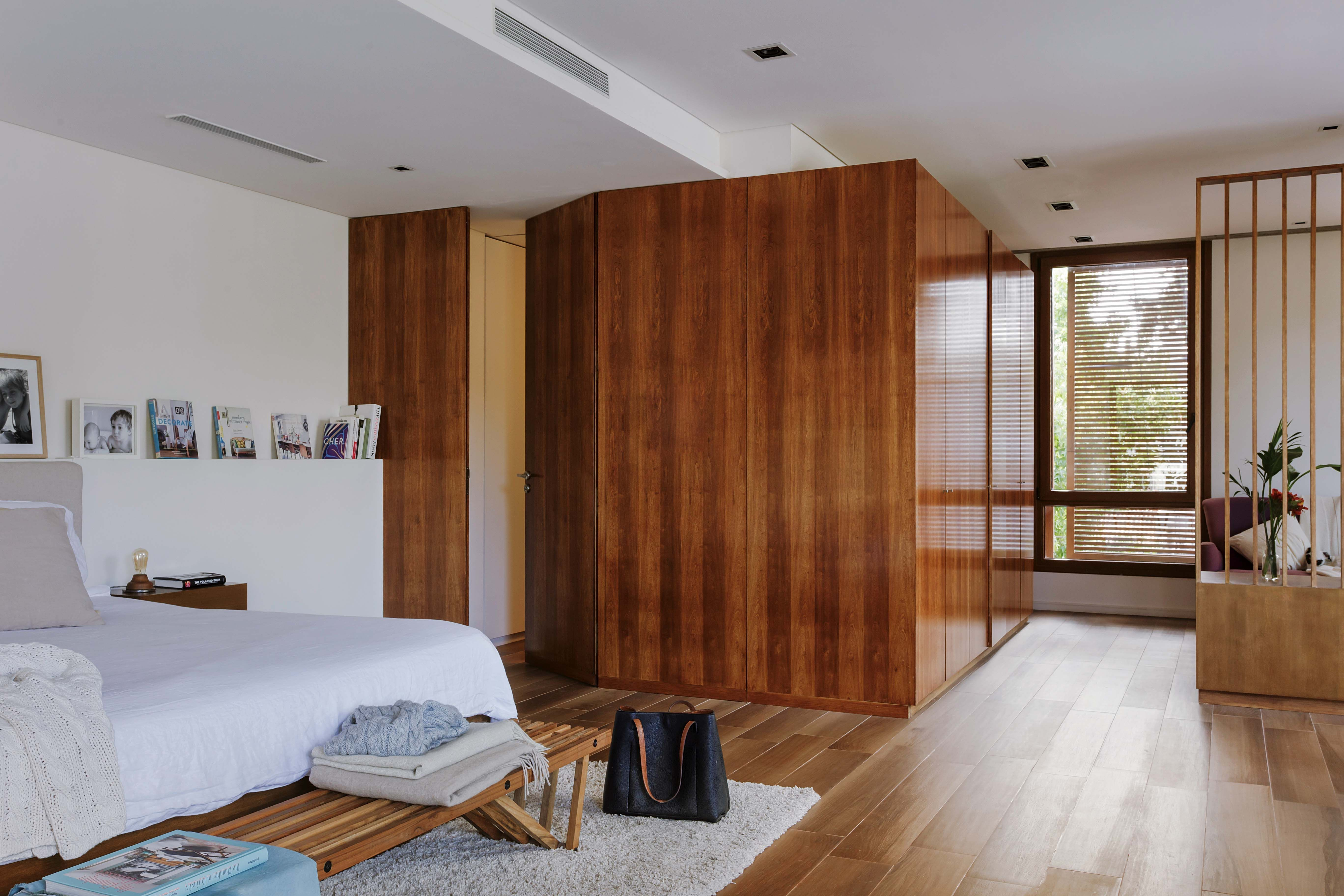 Dormitorio moderno con cama enchapada en madera y cabezal tapizado ...