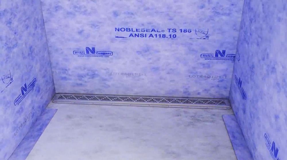 Installation of the FreeStyle Linear Drain with NobleSeal® TS CPE sheet membrane waterproofing on walls and floor.