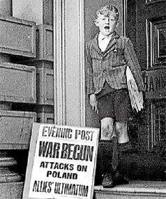 A newspaper boy with a billboard headlining the beginning of World ...
