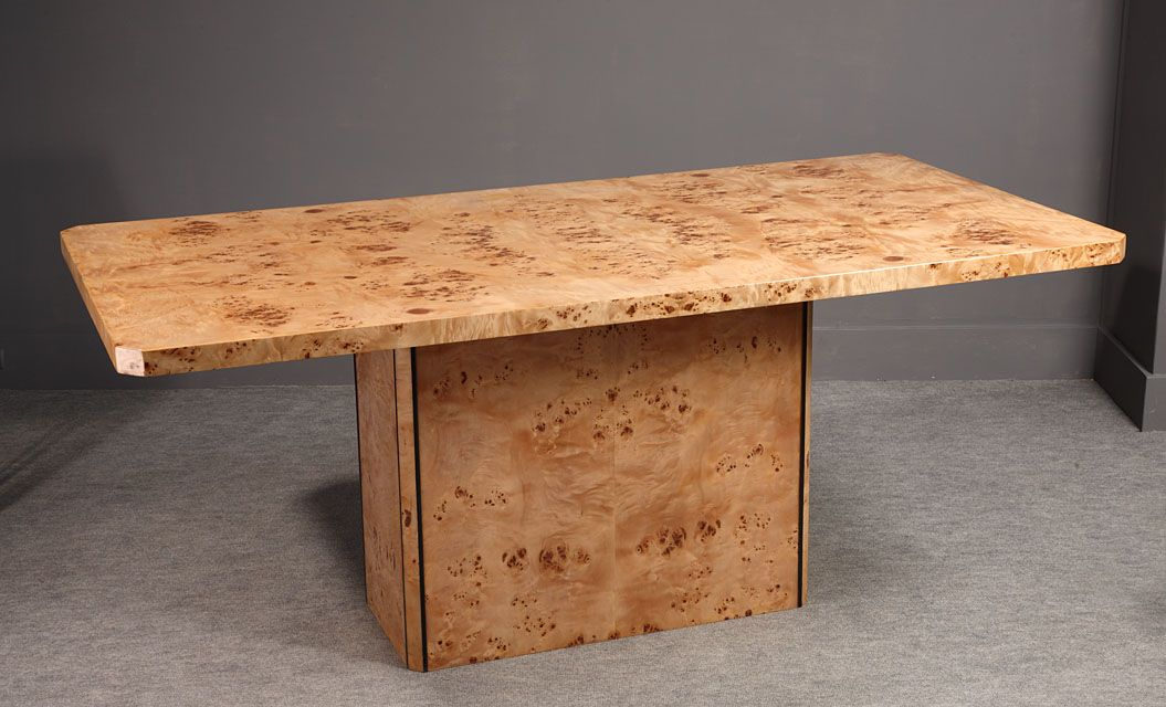 A rectangular elm burr veneer dining room table standing on a