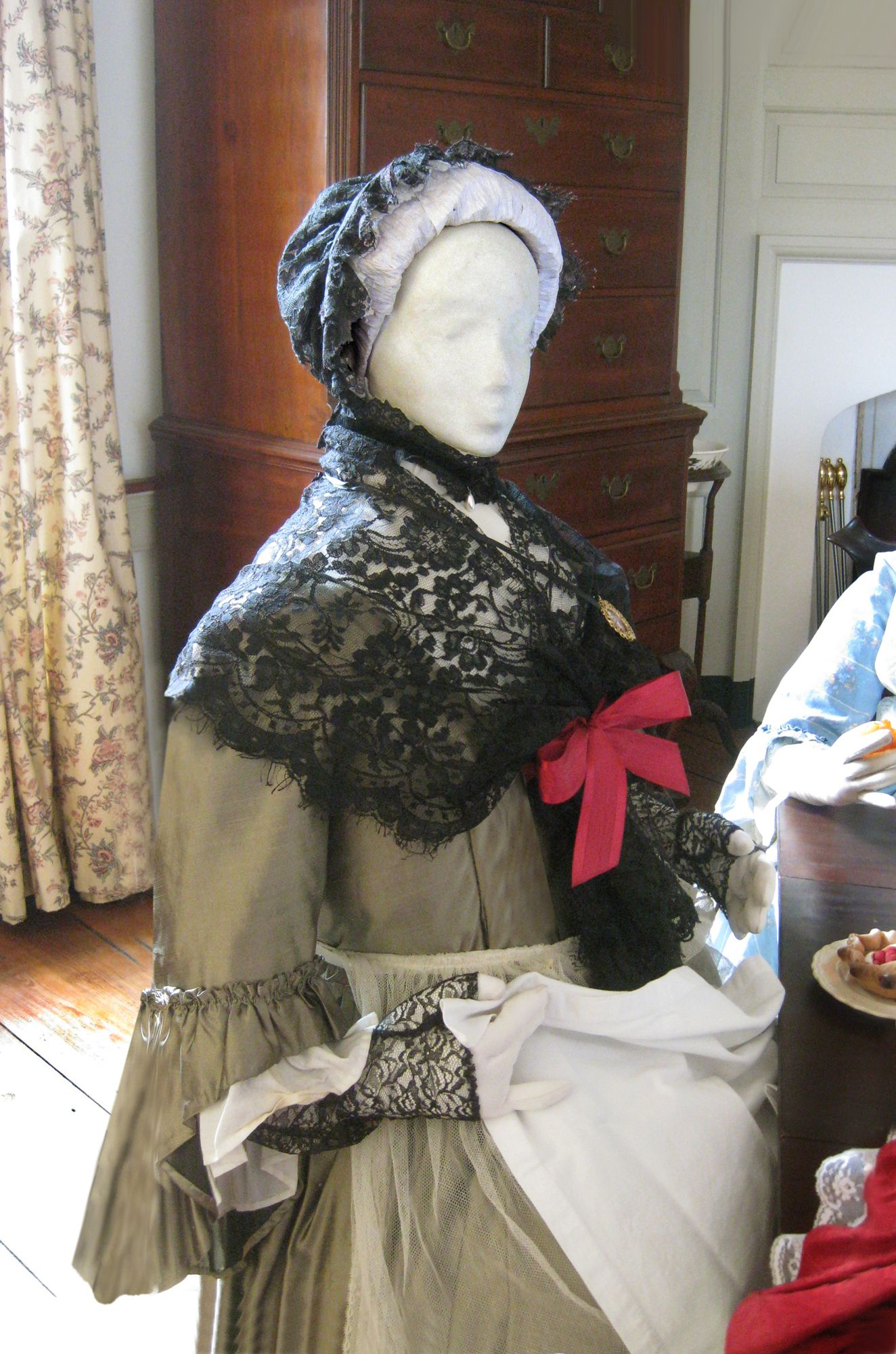 Family matriarch, Anna Savage Nutt, sits between her daughters Ruth and Rebecca. All three women were wed to, or widowed from, husbands who were leading ironmasters in PA. Her clothing reflects the refined taste of an older woman in the late 1750s.