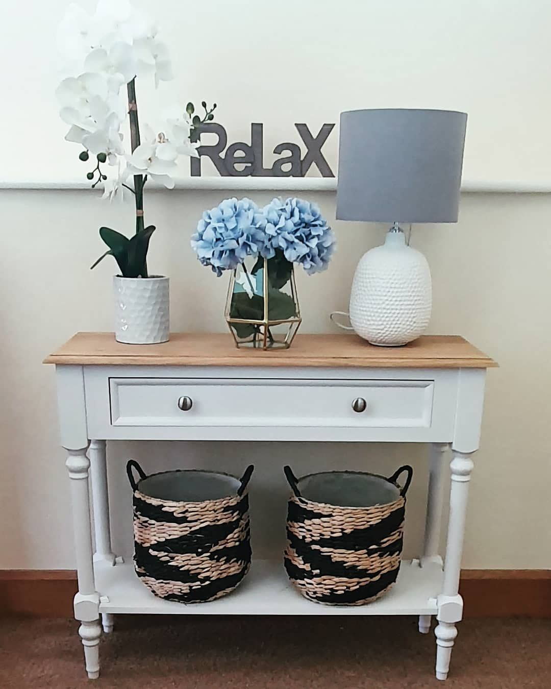 This empty landing area is now beautifully decorated with a white console  and decor accessories in a calming colour scheme ideal for the sleeping area of the house. . . . . . #homedecoracessorize #homedecorinspiration #interiordecorating #interiordecor #homemagazine #dressyourhome #instadecor #interiordecorating #interiordesignerlife #instalifestyle #consoletabledecor #flowervases #tablelamps #relax #blueflowers #rattanbasket #homesweethome #interiors #houseinterior