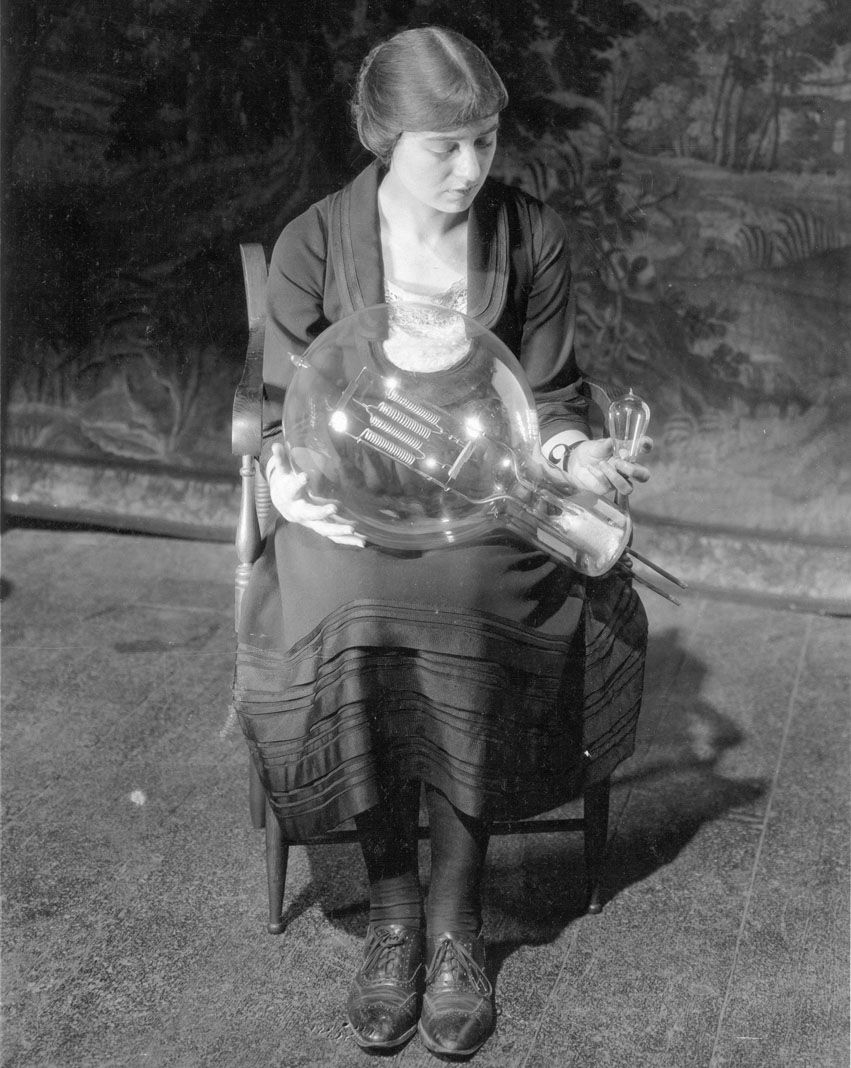 Maude Adams poses with a 25 Watt Mazda lamp and 30 kilowatt incandescent lamp. After Maude Adams retired from acting, she came to Schenectady to work with the General Electric Illuminating Engineering Laboratory on developing new lighitng for theaters. The 30 kW lamp was developed by Adams in conjunction with the laboratory was used in theaters and airports.
