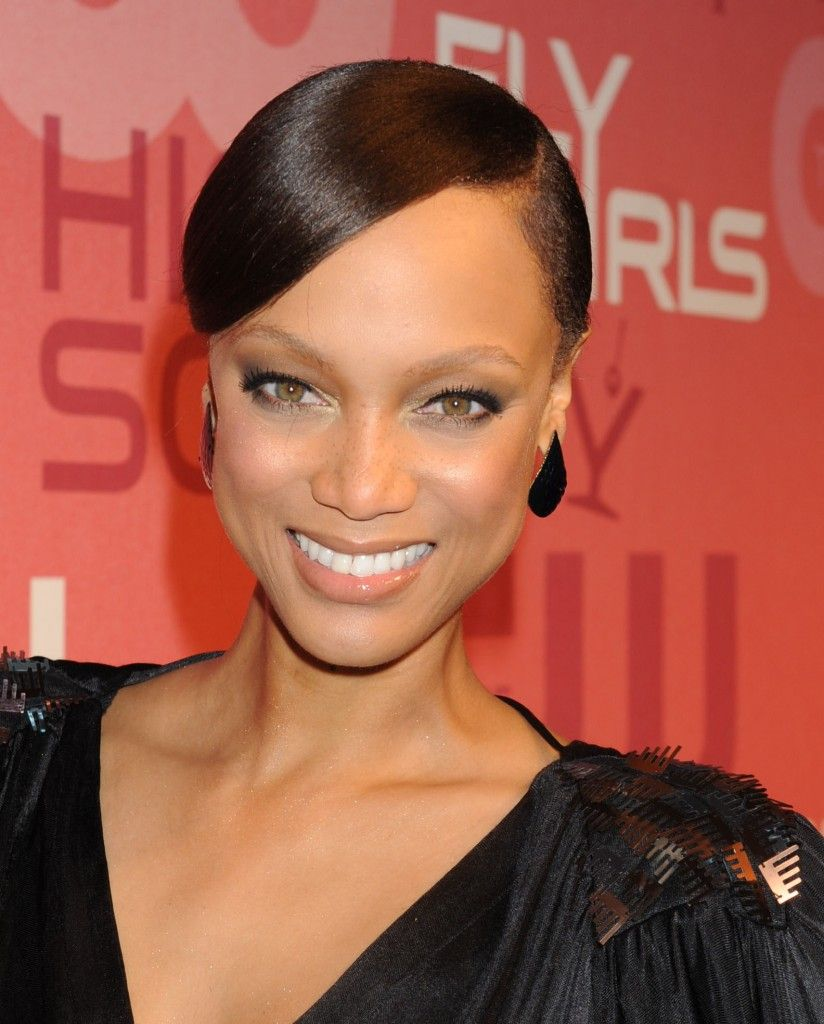 tyra banks wearing a sleek chic low bun hairstyle while attending
