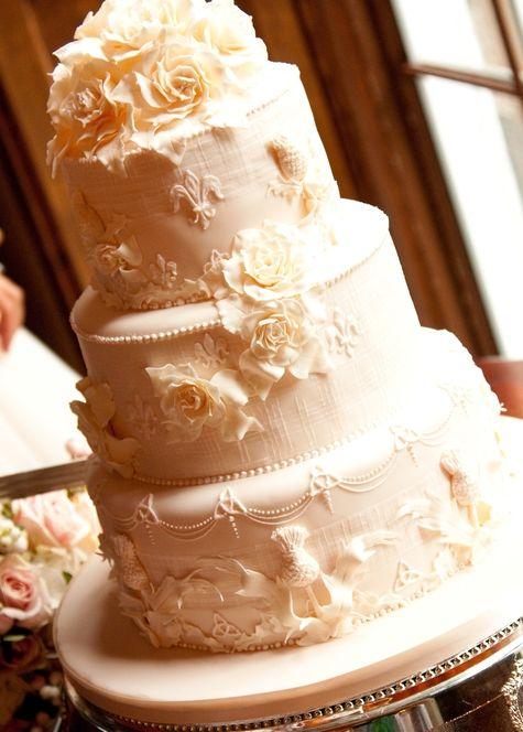 White wedding cake with white sugar flowers, fleur de lis and celtic knots //  Photographer: Philip Stewart