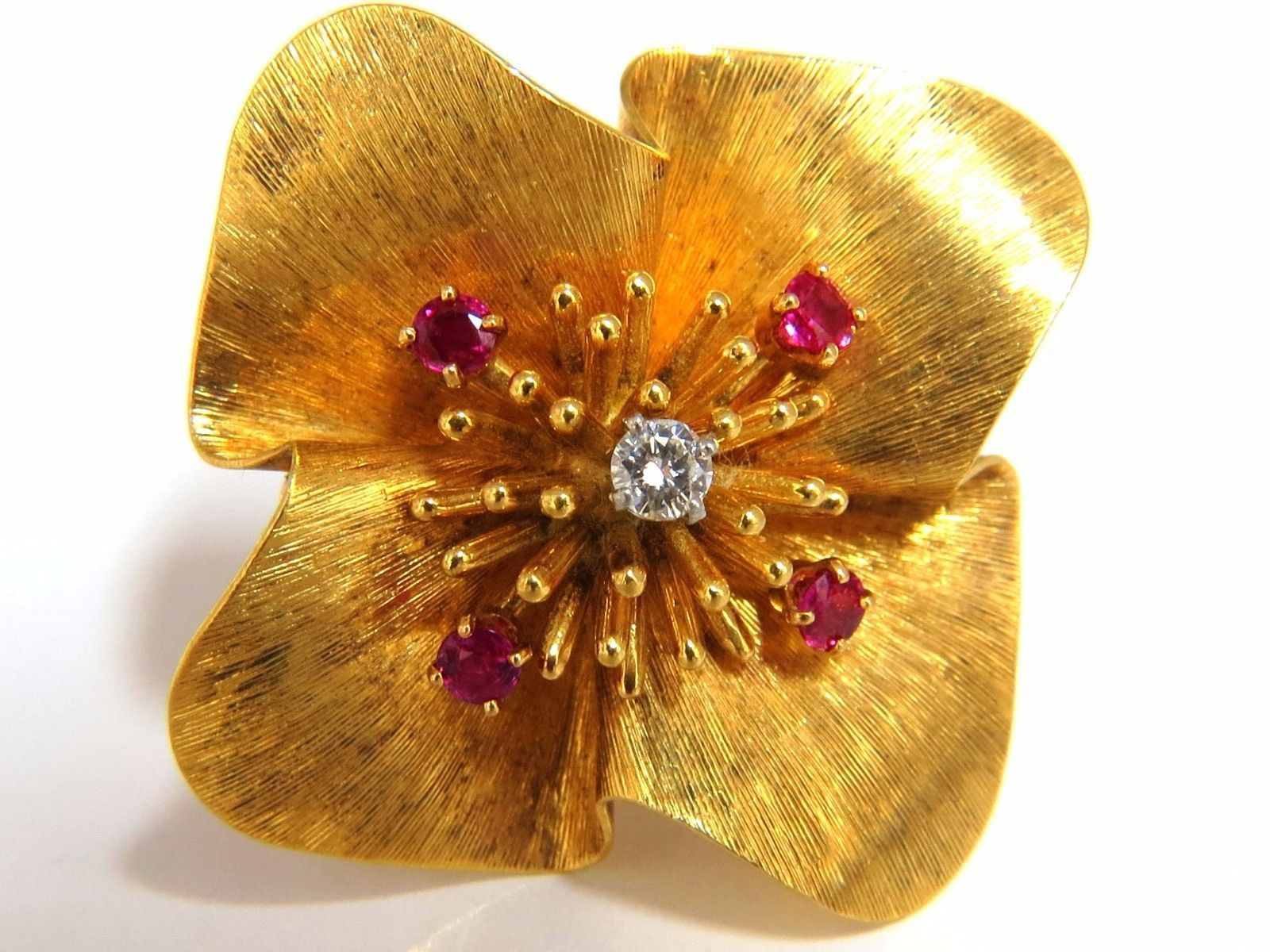 Raised Classic Starburst within petals. .15ct natural diamond. Rounds, Full cut Brilliant. G-color VS-2 clarity. 4 Natural Round Rubies .10ct. 14kt yellow gold intricate brush detail. 17.5 grams. Over