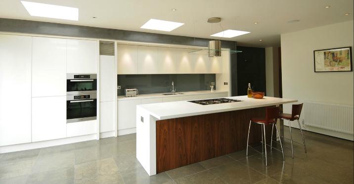 Corian and glass kitchen with walnut storage