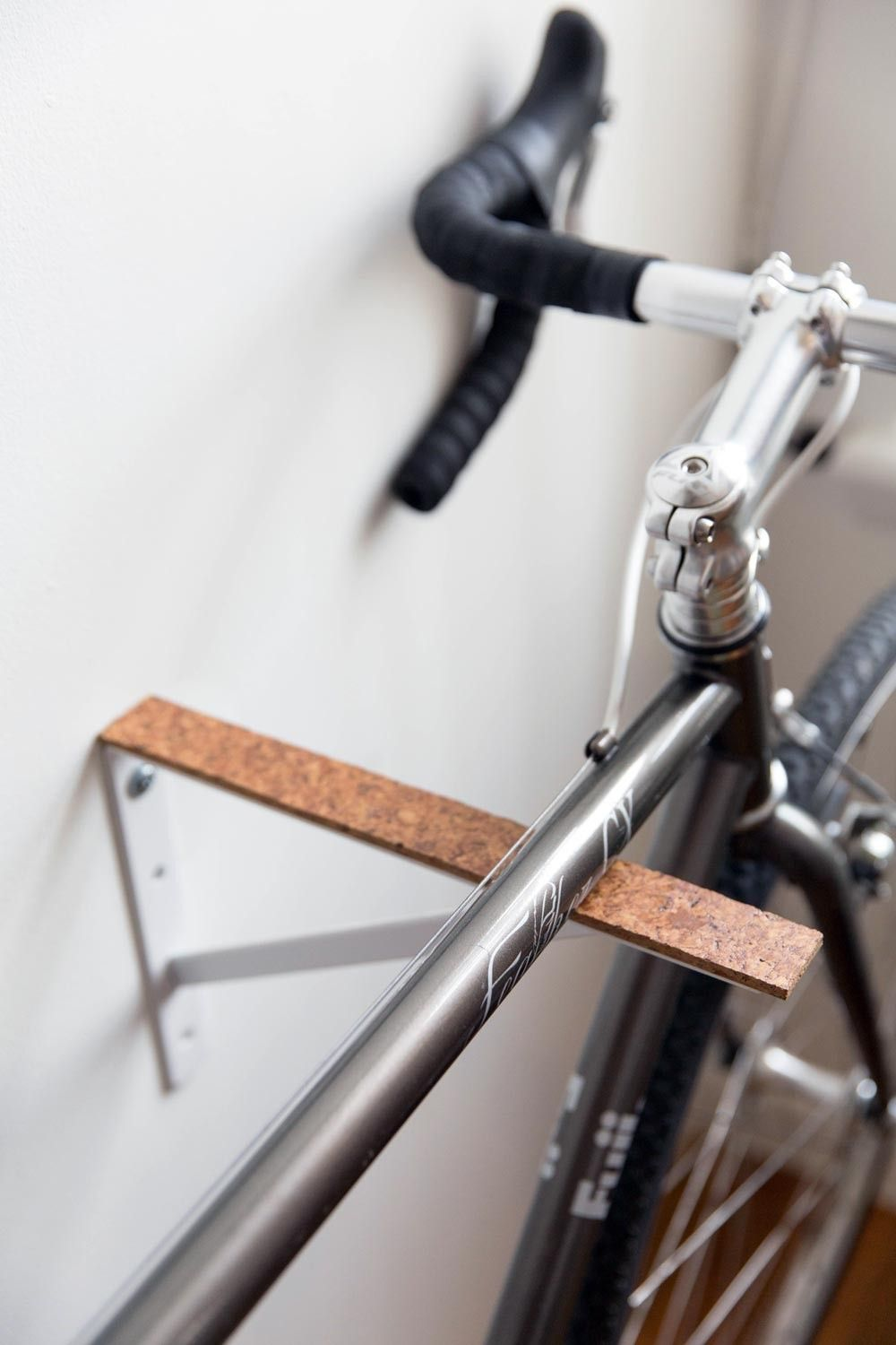 joe made the bike racks from simple inexpensive shelf brackets and thick pieces of cork - Indoor Bike Rack