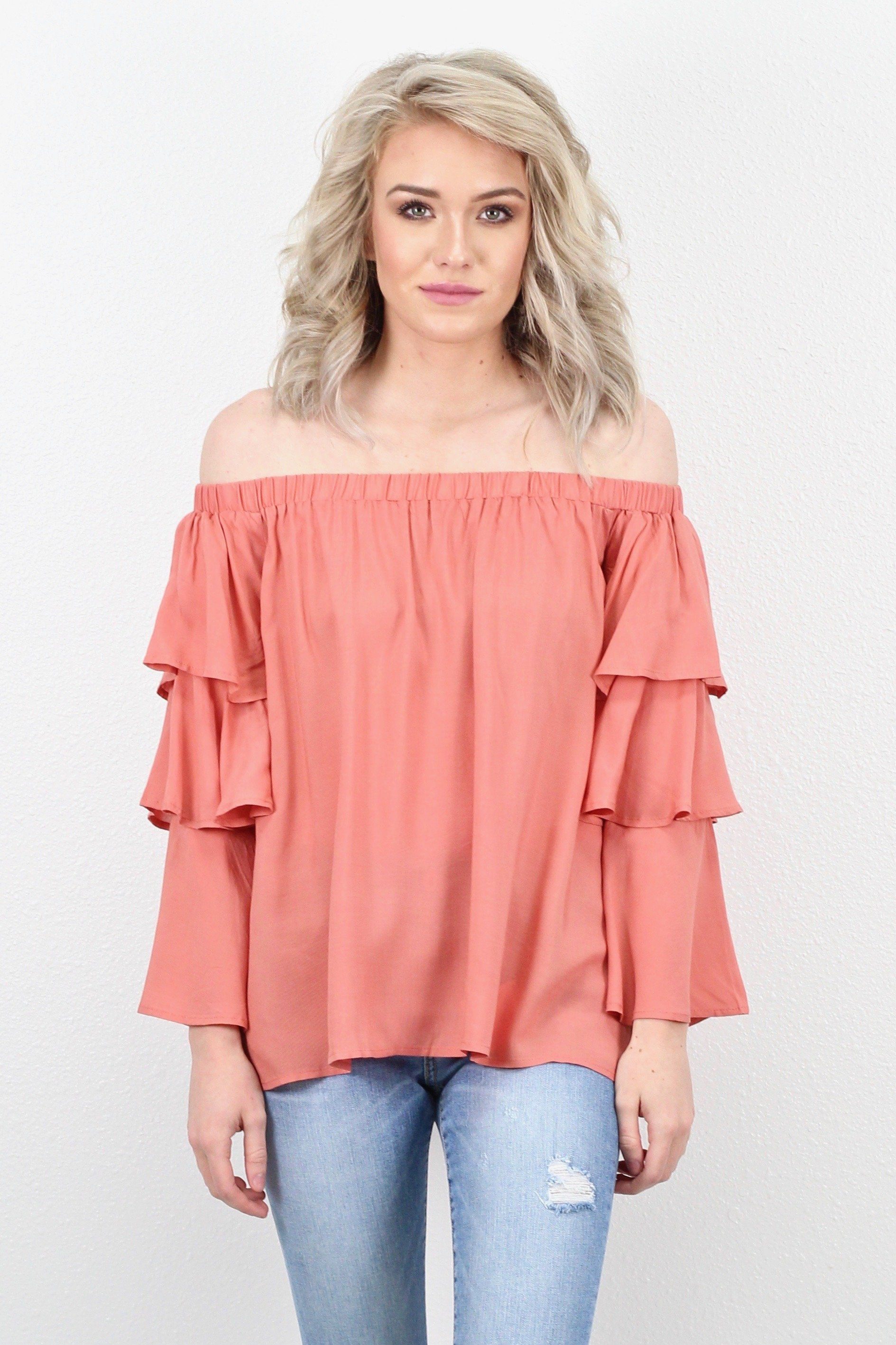 c7dcbc35873 Off shoulder blouse with long sleeves that feature a layered ruffle look.  So cute worn with shorts or denim