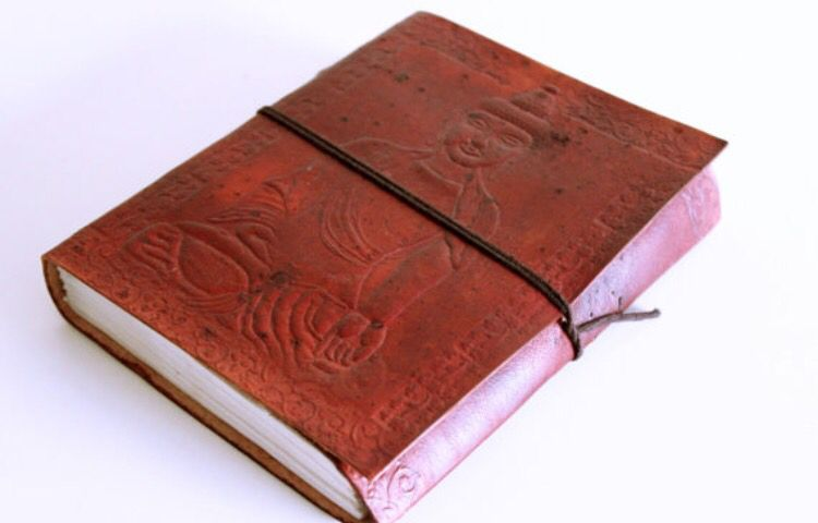 A Unique hand made recycled paper journal or sketch book from India. This piece has beautiful imprint of Buddha on the leather cover and patterns in the front and back of the book.
