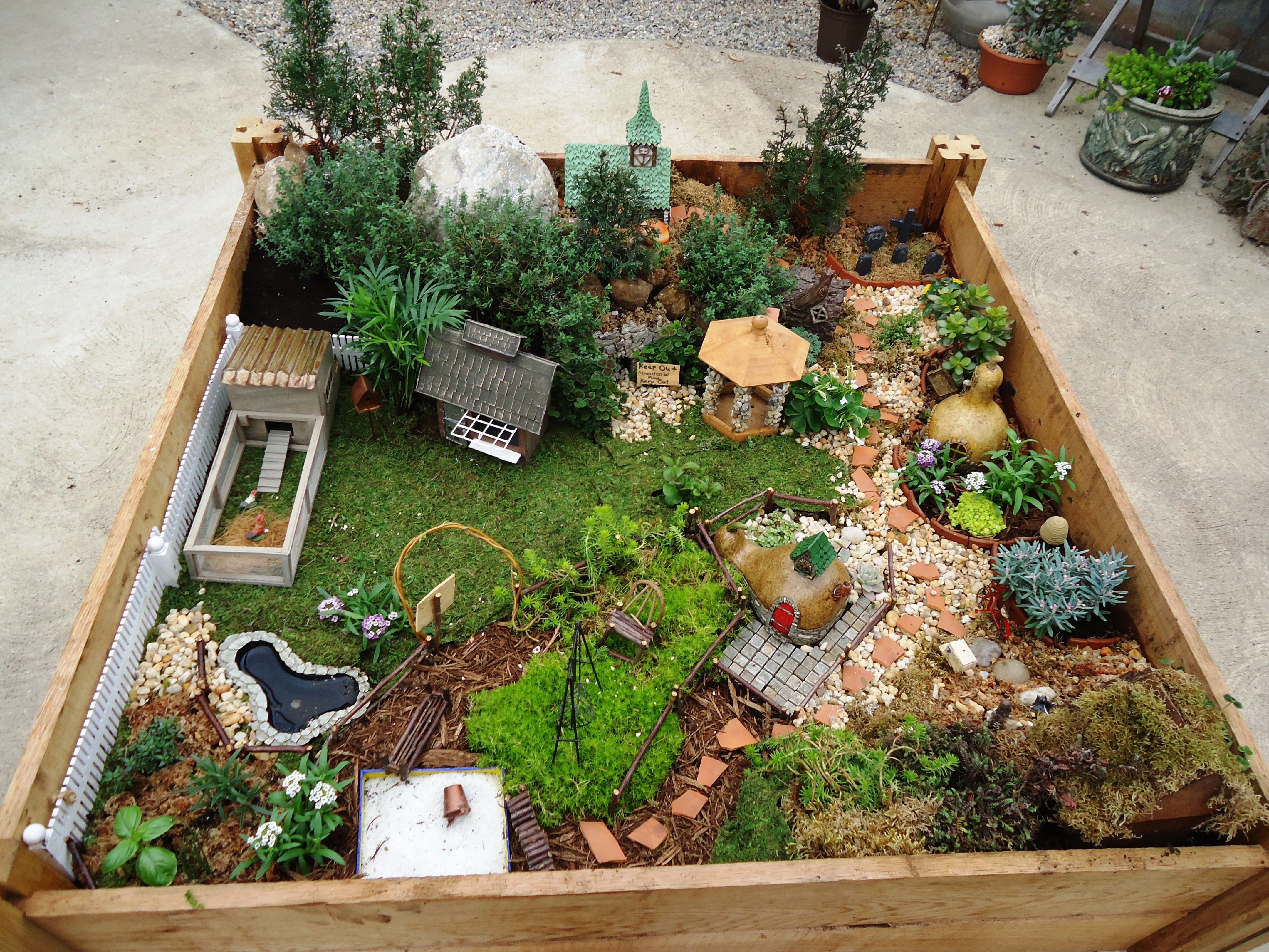 a raised garden bed turned into a fairy village fairy