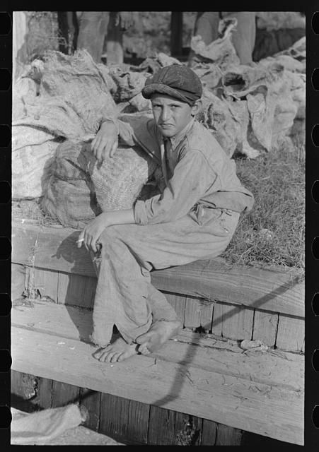 9. You're never too young to learn the family trade, right? This young boy takes a break near some oyster bags (1930s)