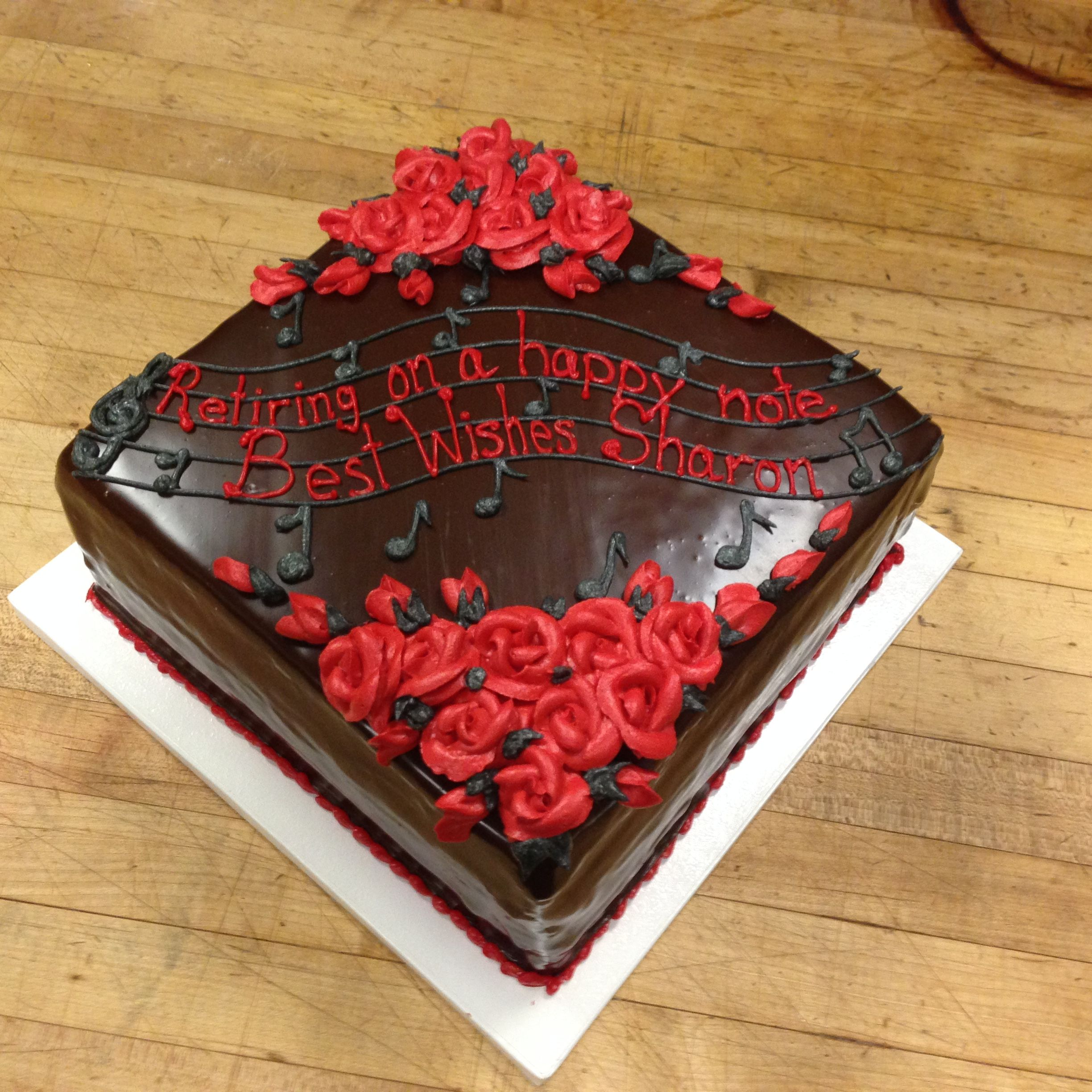 Music Notes Red Rose Design On The Ganache Covered Retirement Cake