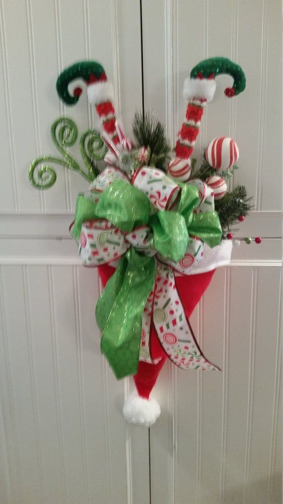 Best 12 A whimsical decoration perfect for a wall or door. This Santa hat is filled with a variety of greens, colorful ribbon and cute elf feet! May vary slightly from picture. Hanger not included. Height: 27 Depth:10 Width: 17