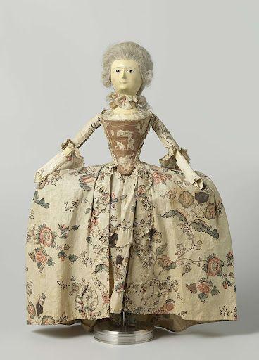 Pop van hout met glazen ogen en kapsel van mensenhaar, gekleed in een japon (demi-parure) van gebloemde sits, bestaande uit een overjapon en een tablier, anoniem, ca. 1760
