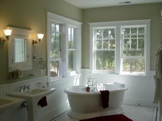 A traditional claw-foot tub with polished chrome fixtures is a focal point in this bathroom, which also features a remote-controlled gas fireplace.