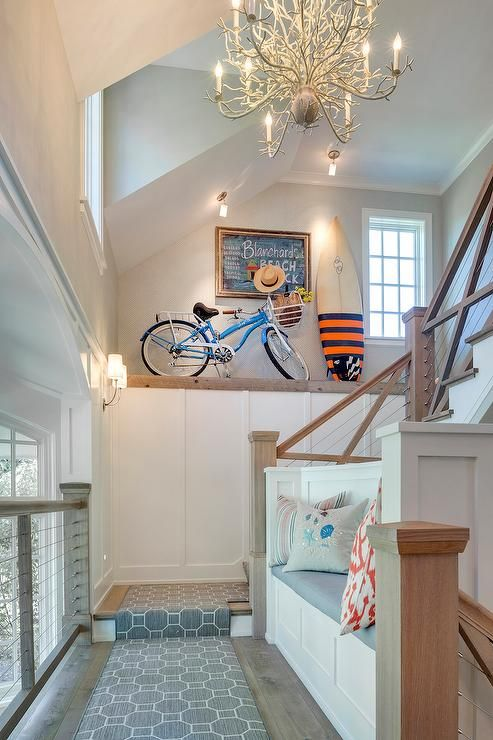 Two story foyer features a white coral chandelier illuminating a two story foyer features a white coral chandelier illuminating a built in bench alongside a gray geometric runner foyer pinterest foyers chandeliers aloadofball Gallery