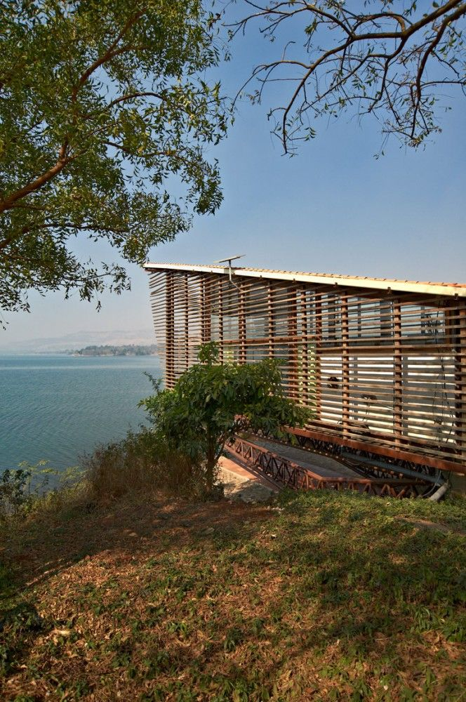 Over Water / Design Workshop, India. The strategy was to build a glass house perched on the land and provide privacy for the inhabitants, at the same time to make sure the lake view gets highlighted from inside for the inhabitants. The structure is wood steel and glass, supported on 2 RCC columns, perched like a bird on land.