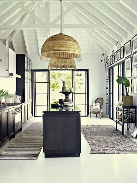 Black and white kitchen warmed by rattan pendants.