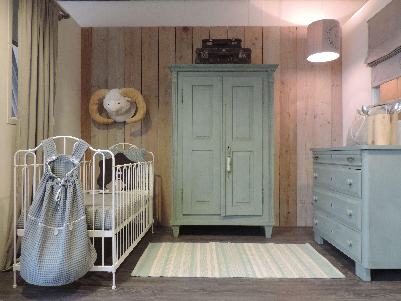 Zachtgroene babykamer met wit smeedijzeren ledikant