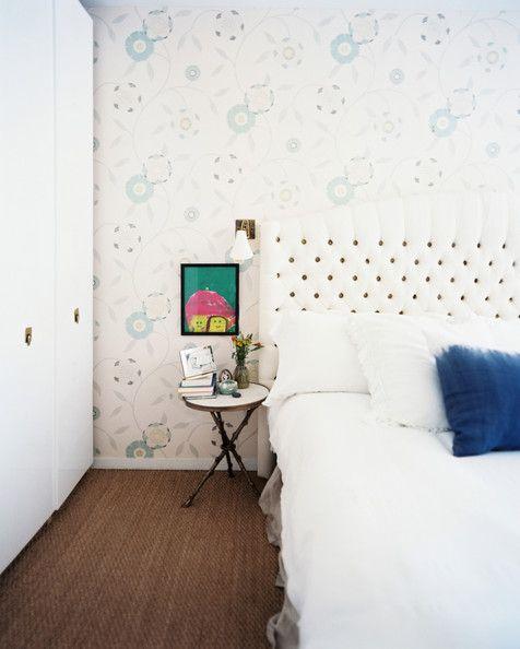 Un dormitorio femenino con papel de flores...