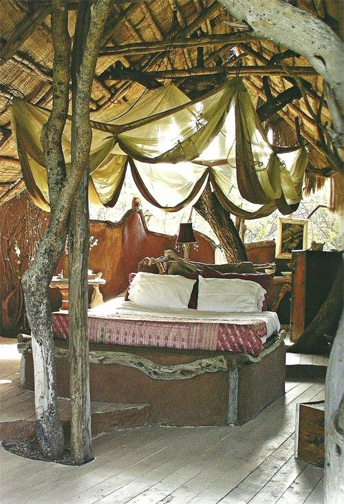 Looks like an attic. and there's a tree in the middle. It's the tree house bedroom of my dreams.
