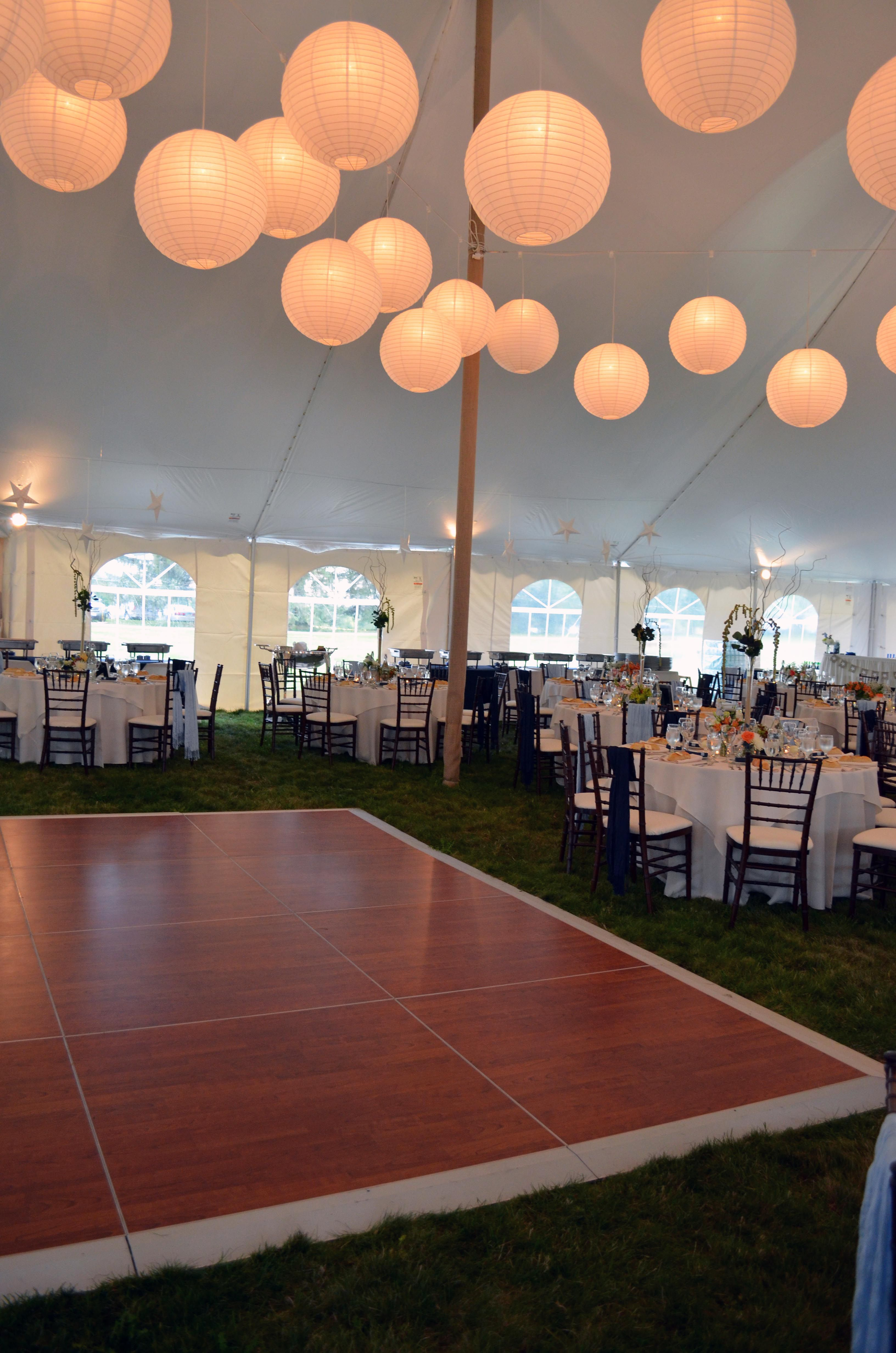 These lanterns add a beautiful glow to an outdoor tent wedding