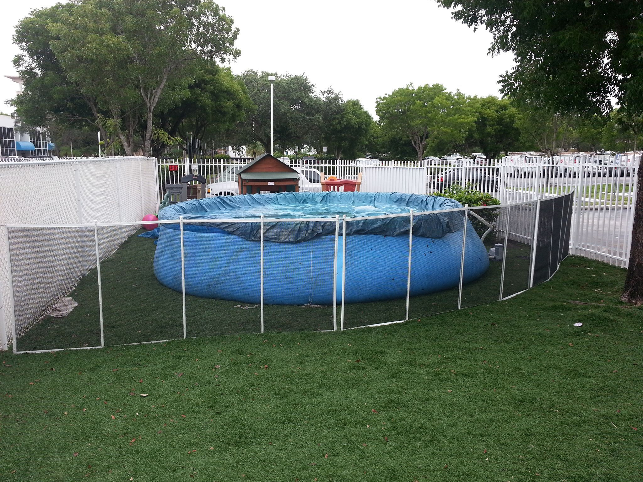black mesh pool fence with white poles installed in grass ...