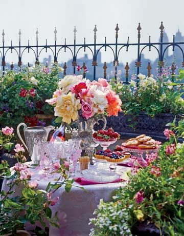 A rich tablecloth and sparkling glass dishes add a feeling of luxury to an outdoor setting. Colorful berry desserts on stands of varying heights and a bouquet of blooms in a vintage silver coffee urn infuse the space with color.