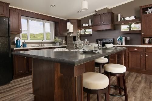 The Dark Wood Cabinets And Grey Counter Tops Give A Sleek, Modern Look To  This