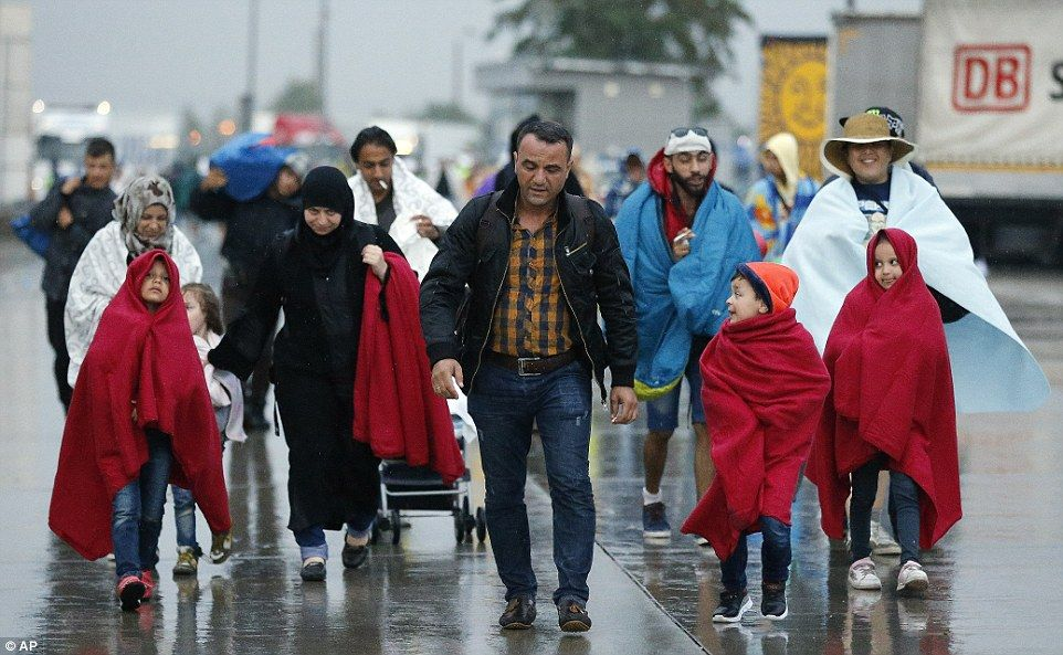 Arrivals: Migrants cloaked themselves in blankets to shield themselves from the pouring ra...