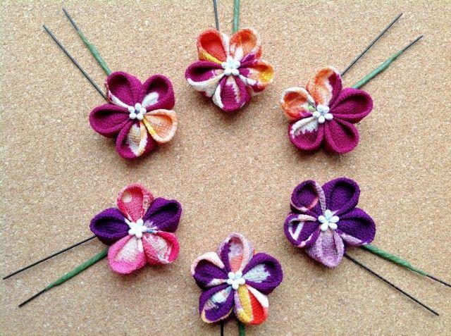 舞妓さんのかんざしなどに使われている「つまみ細工」。  「つまみかんざし」とも呼ばれる伝統工芸の技法を用い、小さな布を折り紙のようにたたんで、立体的なお花を作っています。  今回は、花火大会などに使いたい純和風な雰囲気の縮緬という生地でお作りしました。  上3本は赤紫系、下3本は紫系です。  素材はレーヨンちりめん。 京都の友禅工場に保管されていた40年ほど前の型を使い、 手捺染という、人の手により染める技法で染め上げられた古典復刻柄の生地。  発色の良さに一目惚れして購入しました。  シボ(でこぼこ)の細かな一越ちりめんです。  花芯は、パールの光沢感のある白です。  着物や浴衣にいかがでしょうか。 可愛らしい雰囲気なので、お若い方や、お子様にも良いかもしれません。  柄の出方が異なるため、全て一点限りとさせていただきます。