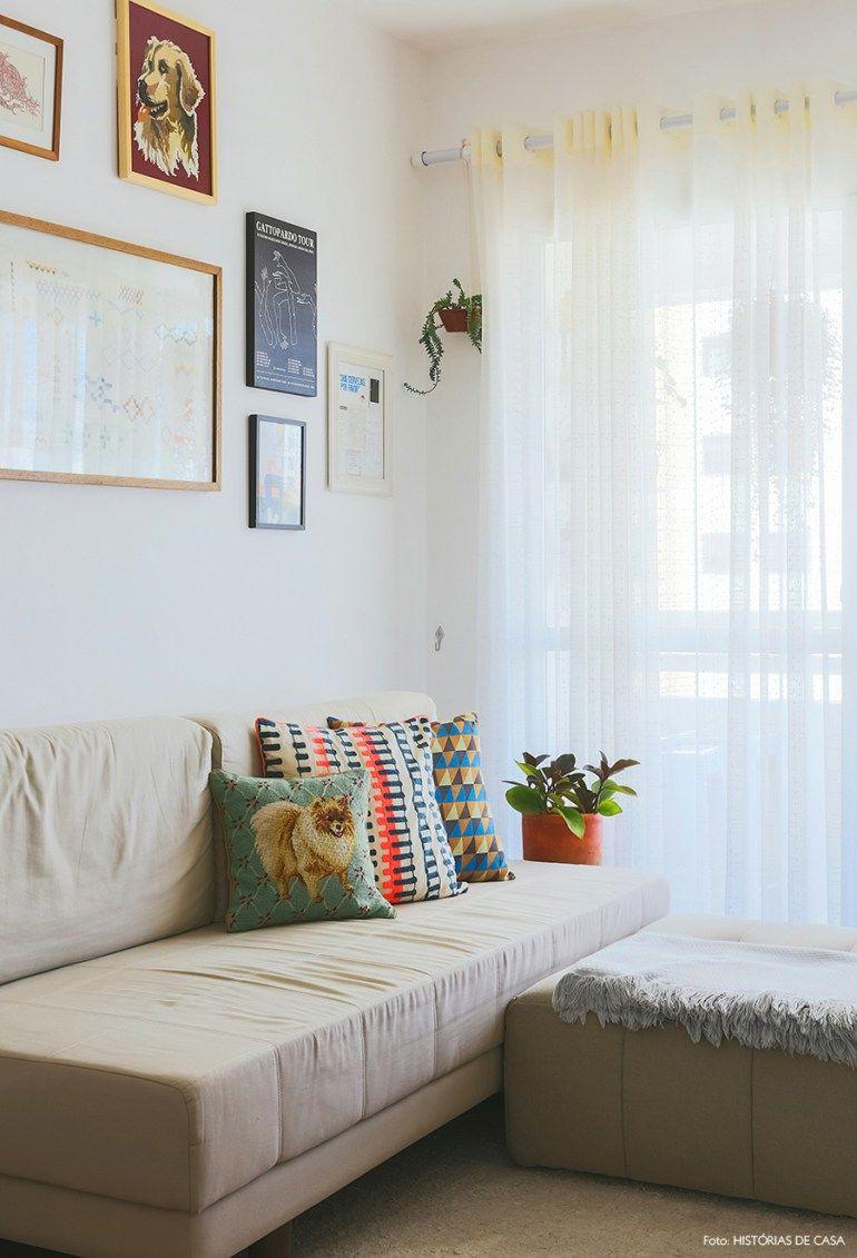Sala de estar com sofá e puff bege e almofadas coloridas e estampadas.