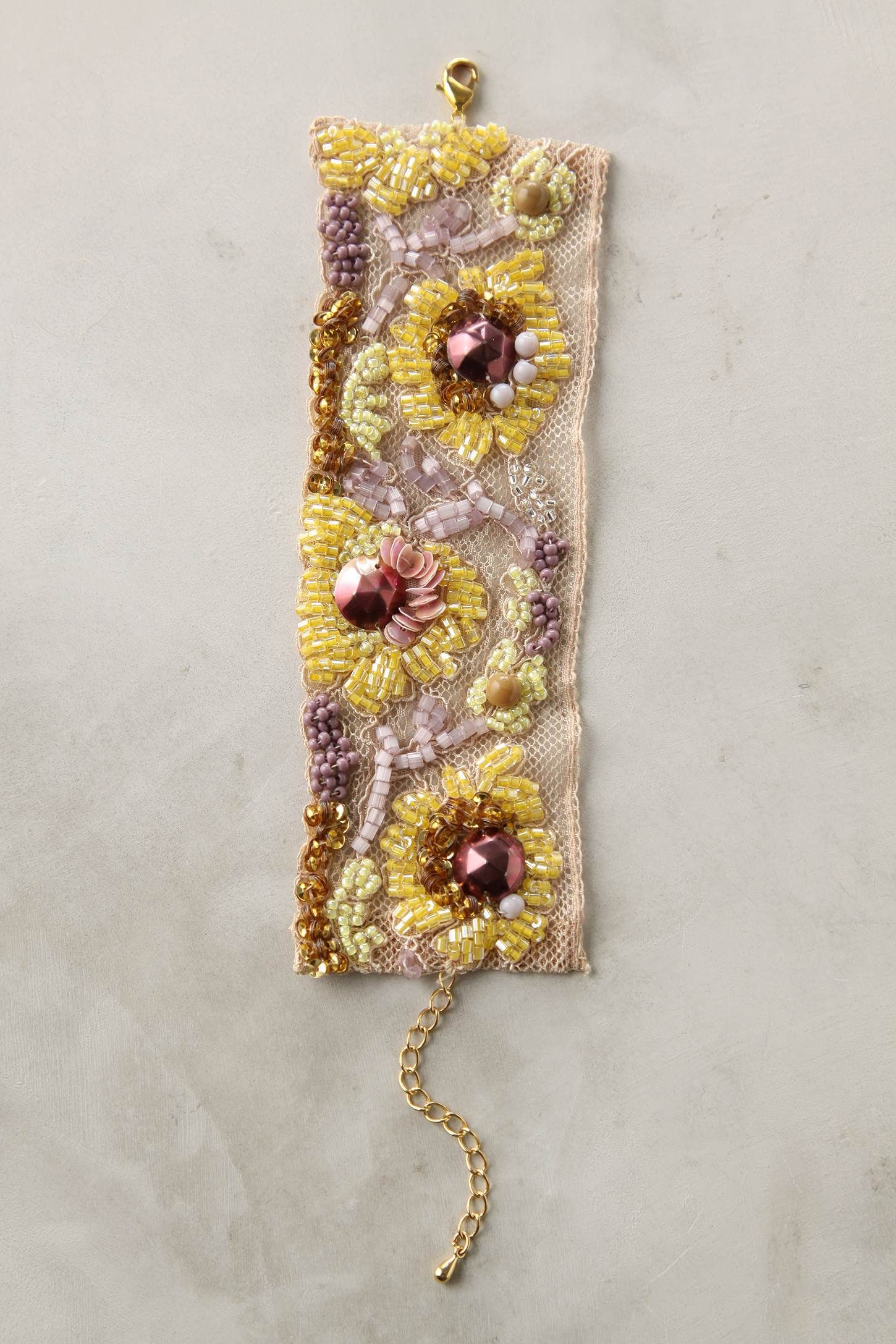 Handmade Pomponette bracelet with faceted gems, sequins, and beads atop vintage lace #jewelry