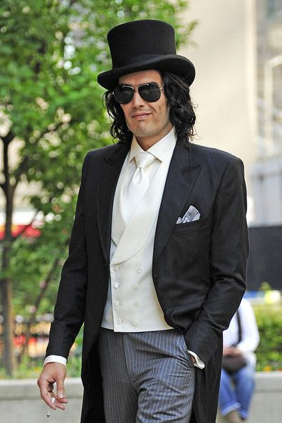 7bf02d75566d2 Russell Brand was spotted on set wearing a tailcoat with a classic black  top hat.