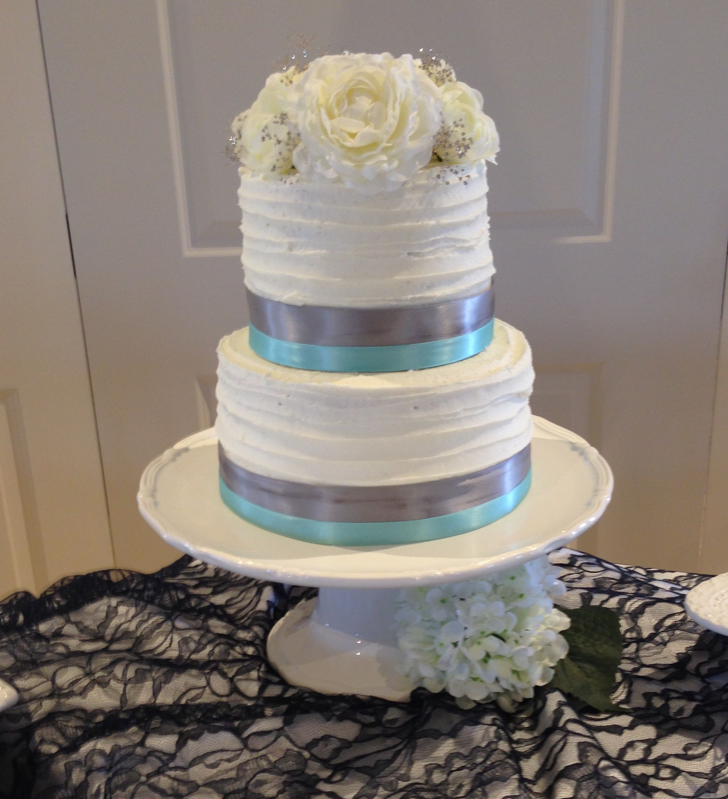 Tier white wedding cake rustic iced with mint green and silver