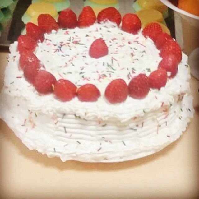 Vanilla cake with whipped cream frosting topped with strawberries and candy sprinkles