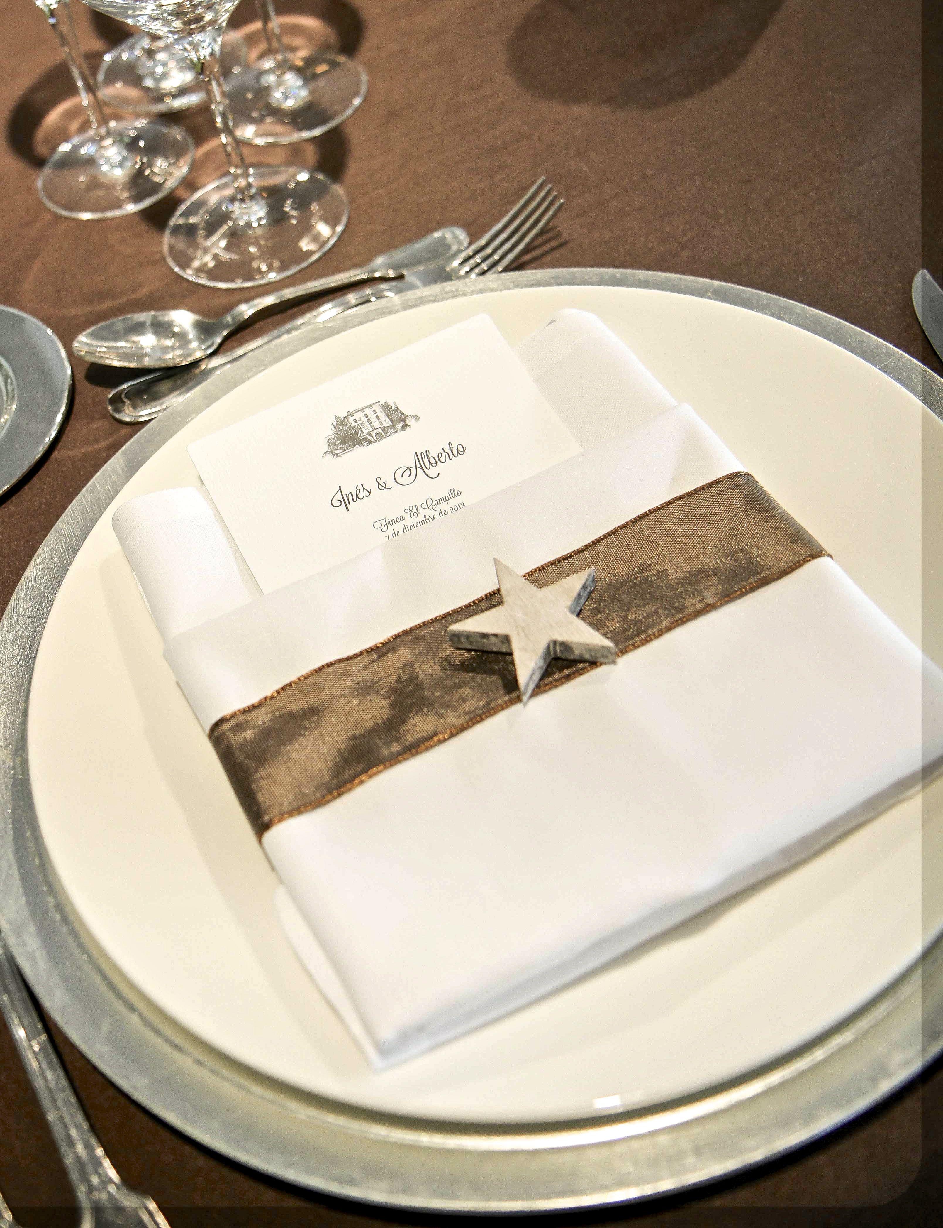 Minuta envuelta con cinta de raso marrón y estrella de madera para una boda invernal.