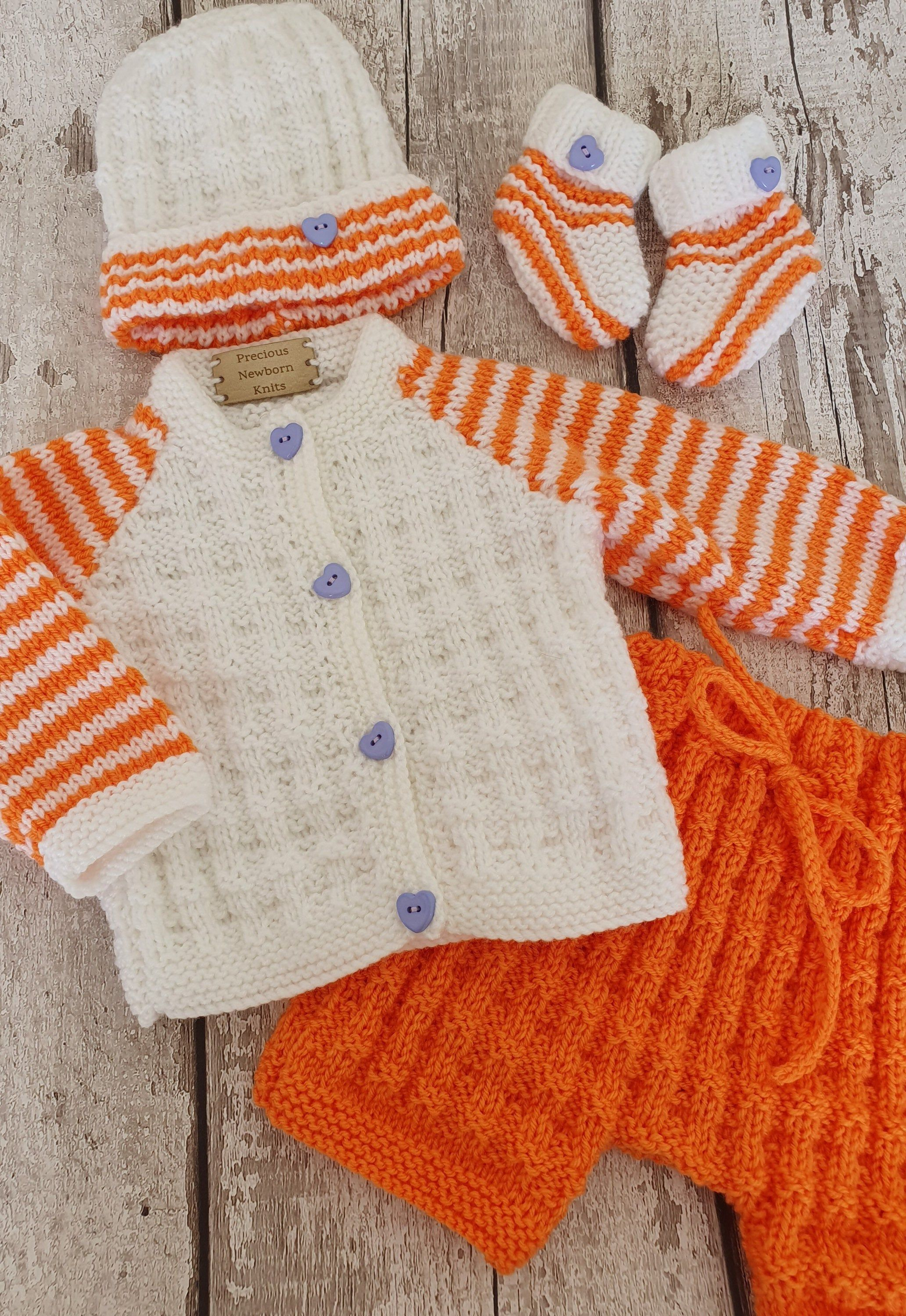 Handknitted baby sweater booties and hat