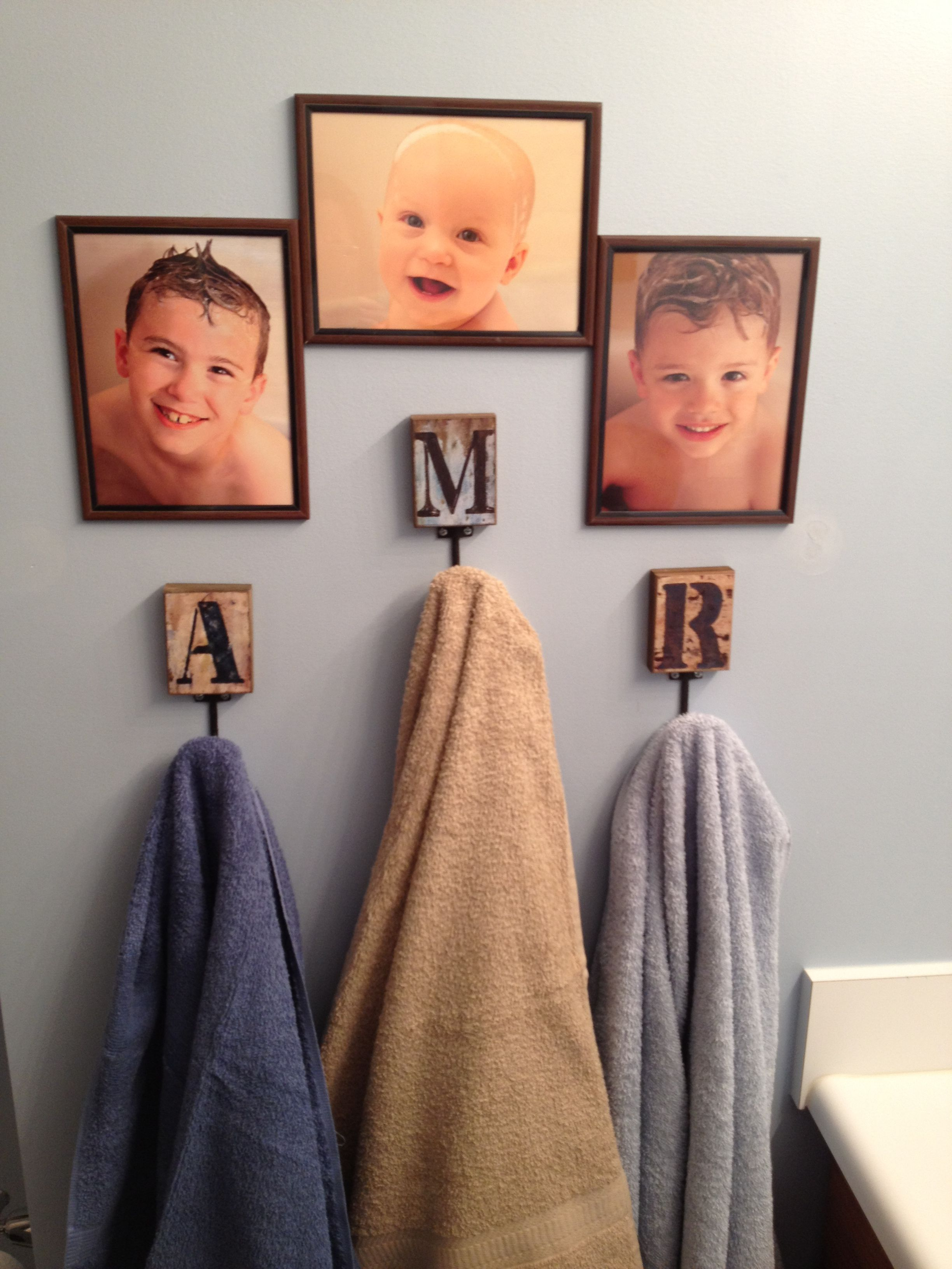Decorating a kids bathroom - took close up face shots only of them with wet heads and bubbles and framed their pictures above a monogrammed hook with their first initial to hang their towels from.