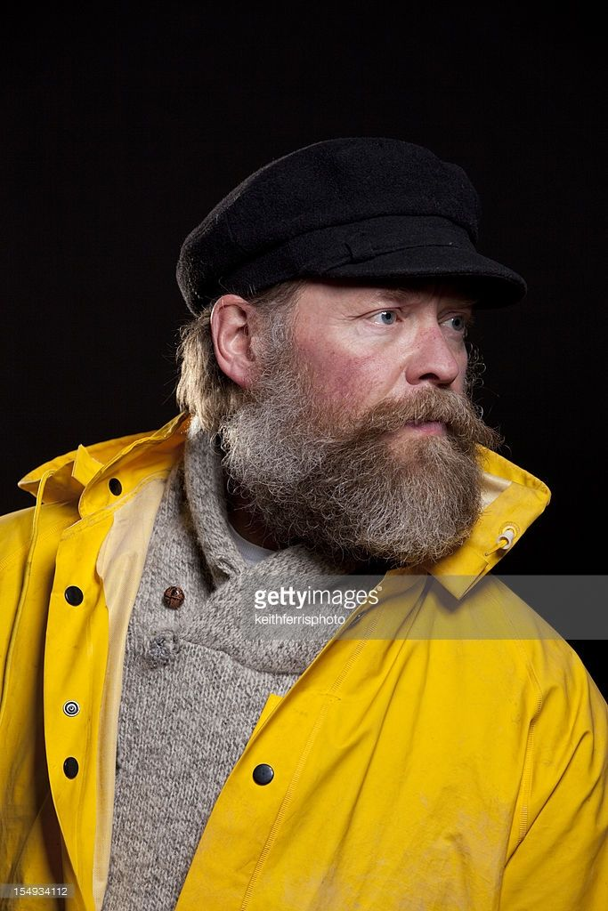 d6ff65d146e03 A middle aged fisherman wearing a yellow rain slicker and a hat with a big  beard.