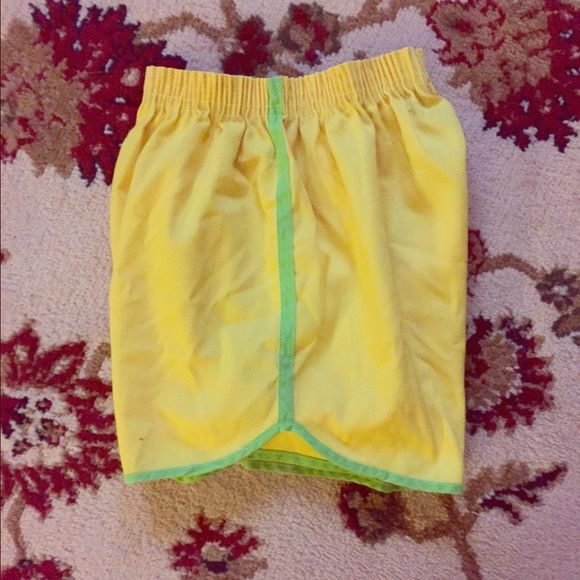 High waisted yellow athletic shorts Cute vintage athletic shorts bright yellow with lime stripe. High waisted. No tag but I can measure! I think they would fit best a size 4. Vintage Shorts