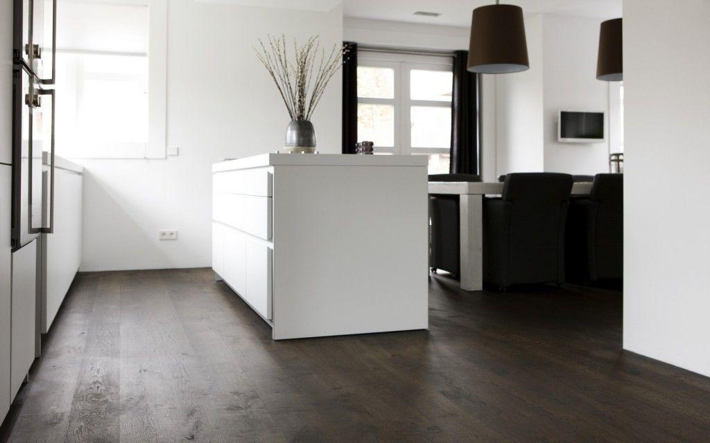 Mooie donkere houten vloer gecombineerd met een heel witte keuken