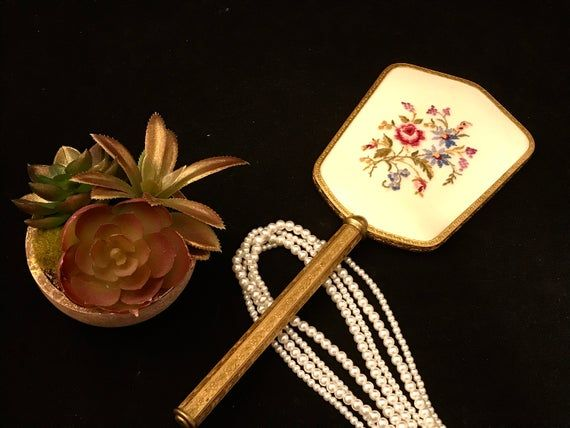 This is such a pretty and feminine petit point floral hand mirror. The hexagonal shaped handle is gold tone with beautiful floral detail. There is a lucite cover over the petit point. Measurements: Mirror is 14