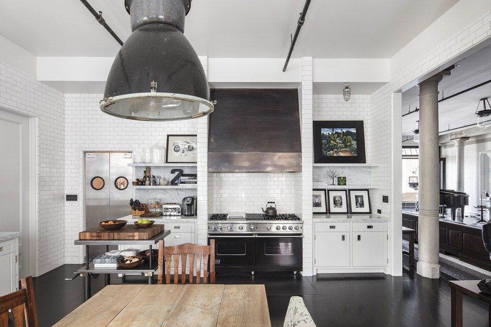Black pendant light over huge farmhouse table, white cabinets, subway tile, and industrial home decor in Meg Ryan loft.