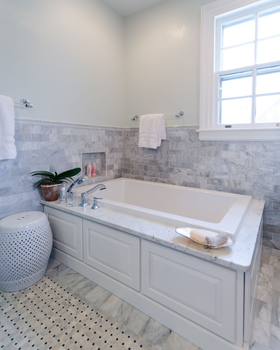 Built-in jacuzzi tub with marble tile wainscoting and custom tile ...