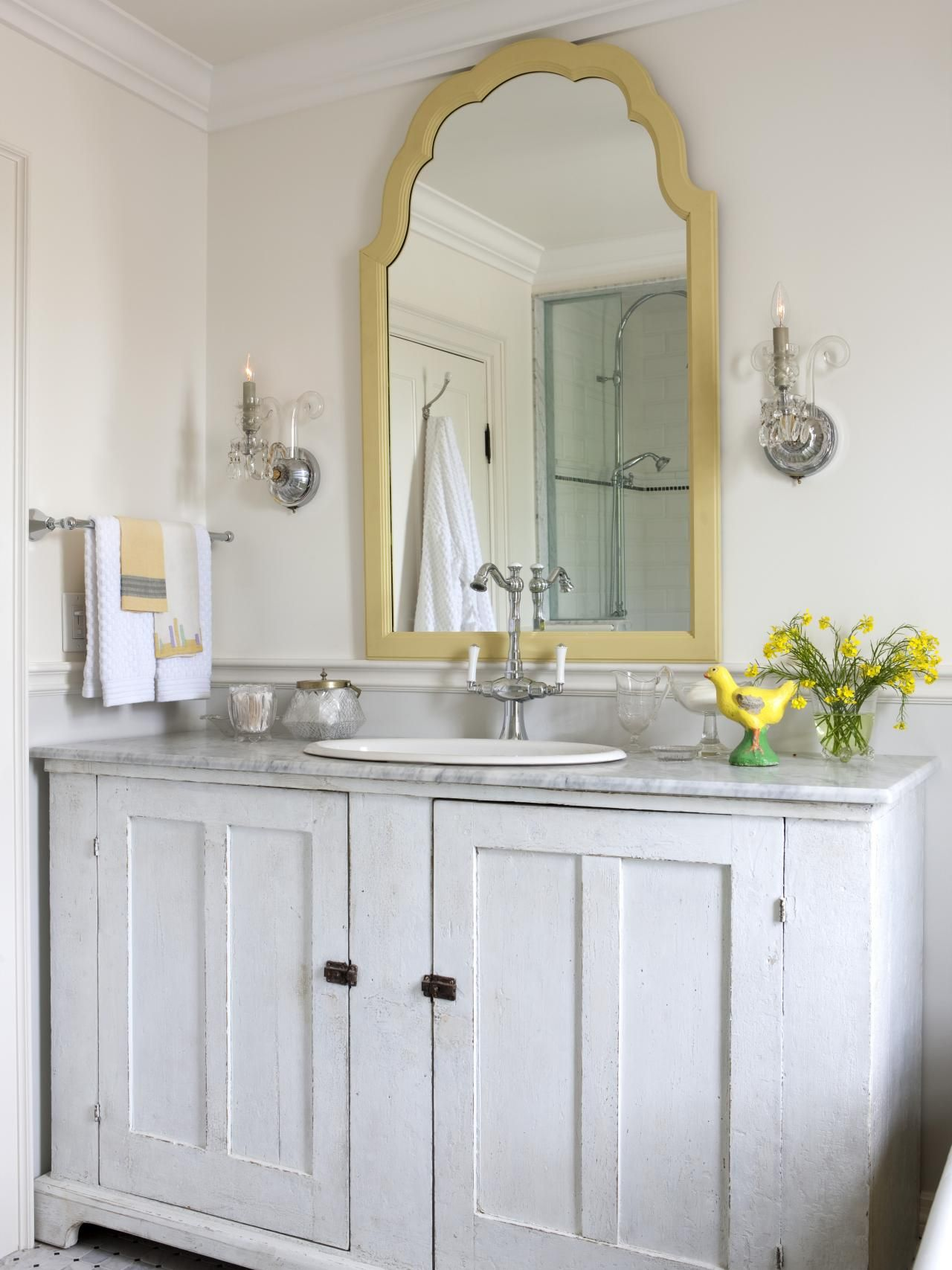 This traditional white bathroom features a gold trim mirror chrome